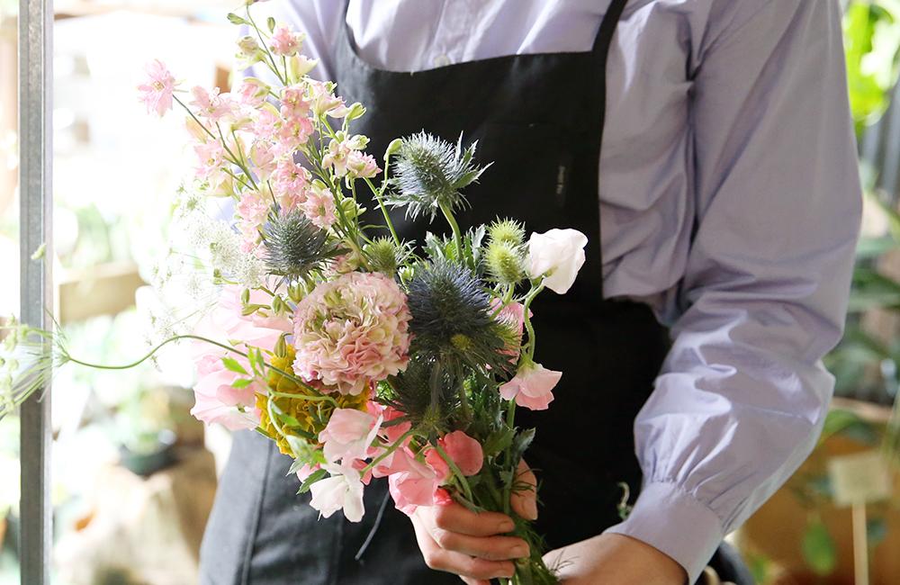 花を持つ店員